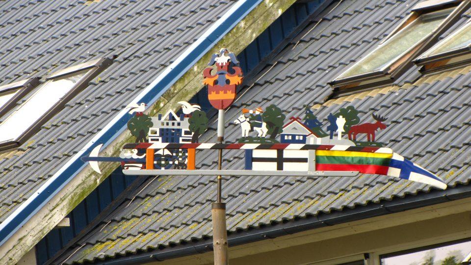Nida. Banderuola con i simboli della composizione della famiglia.